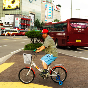 A photo of a South Korean man riding a bicycle in downtown Seoul.